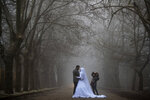 A bride and her groom pose for a photograph during a wedding photoshoot as heavy fog envelope the Sawfar village, Mount Lebanon Governorate of Lebanon, Saturday, April 3, 2021. Lebanese authorities imposed a three-day nationwide curfew as of Saturday morning to try limit the spread of COVID-19 during the Easter holidays. (AP Photo/Hassan Ammar)