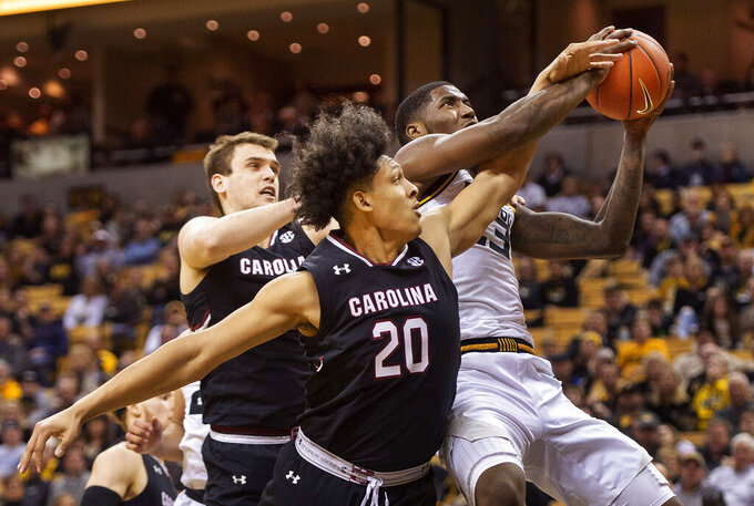 Missouri's Jeremiah Tilmon, right, pulls down a rebound in front of South Carolina's Alanzo Frink, center, and Felipe Haase, left, during the second half of an NCAA college basketball game Saturday, March 2, 2019, in Columbia, Mo. Missouri won the game 78-63. (AP Photo/L.G. Patterson)