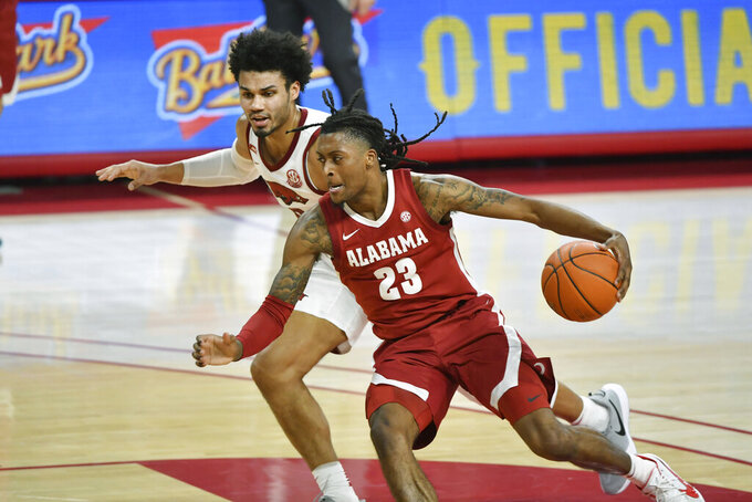 Alabama guard John Petty Jr. (23) tries to drive past Arkansas forward Justin Smith (0) during the second half of an NCAA college basketball game in Fayetteville, Ark., Wednesday, Feb. 24, 2021. (AP Photo/Michael Woods)
