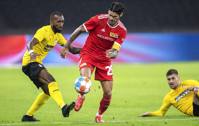 Rangel of Kuopio PS, left, fights for the ball against Berlin's Christopher Trimmel during the Europa Conference League second leg play-offs soccer match between Union Berlin and Kuopio PS, at the Olympiastadion in Berlin, Thursday, Aug, 26, 2021. (Andreas Gora/dpa via AP)