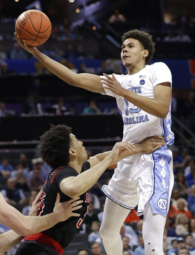 North Carolina's Cameron Johnson (13) drives against Louisville's Jordan Nwora (33) during the first half of an NCAA college basketball game in the Atlantic Coast Conference tournament in Charlotte, N.C., Thursday, March 14, 2019. (AP Photo/Chuck Burton)