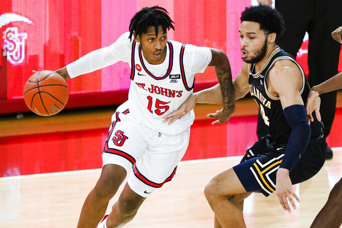 St. John'sVince Cole, left, drives against Villanova's Caleb Daniels during the first half of an NCAA college basketball game Wednesday, Feb. 3, 2021, in New York. (AP Photo/Frank Franklin II)