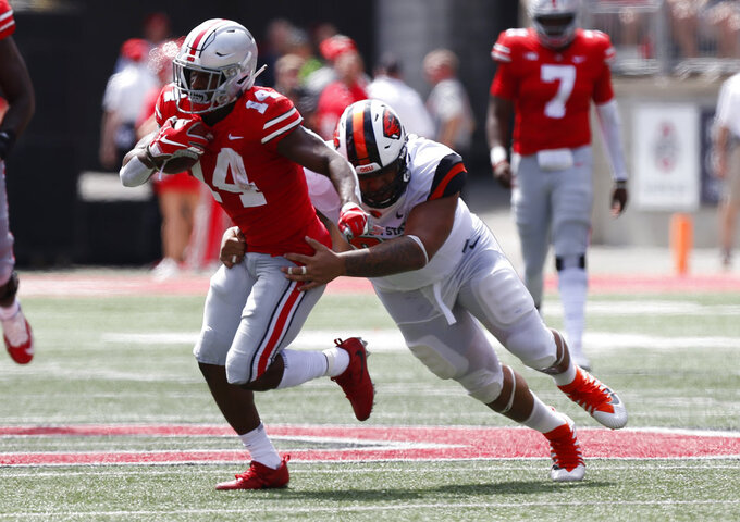 Ohio State receiver K.J. Hill tries to get away from Oregon State defensive lineman Kalani Vakameilalo during the first half of an NCAA college football game Saturday, Sept. 1, 2018, in Columbus, Ohio. (AP Photo/Jay LaPrete)