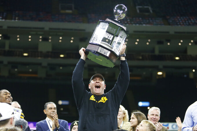 Appalachian State coach Shawn Clark holds the trophy after the team's win over UAB in the New Orleans Bowl NCAA college football game in New Orleans, Saturday, Dec. 21, 2019. Appalachian State won 31-17. (AP Photo/Brett Duke)