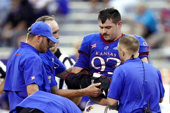 Kansas defensive lineman Sam Burt (93) is helped off the field after an injury during the first half of an NCAA college football game against South Dakota Friday, Sept. 3, 2021, in Lawrence, Kan. (AP Photo/Charlie Riedel)