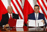 U.S. Vice President Mike Pence and Polish Prime Minister Mateusz Morawiecki, right, exchange copies of an agreement they signed in Warsaw, Poland, Monday, Sept. 2, 2019. The U.S. and Poland signed an agreement on Monday to cooperate on new 5G technology amid growing concerns about Chinese telecommunications giant Huawei. in Warsaw, Poland, Monday, Sept. 2, 2019.(AP Photo/Czarek Sokolowski)