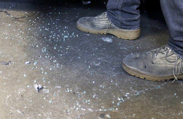 FILE - In this May 12, 2016, file photo, broken glass from a car window is shown on the ground after the car was broken into, at Auto Glass Now, a car in a garage in San Francisco across from police headquarters. A surge of thefts from vehicles parked at tourist locations on the west side of Los Angeles has been linked to San Francisco Bay Area gang members, authorities say. (AP Photo/Jeff Chiu, File)