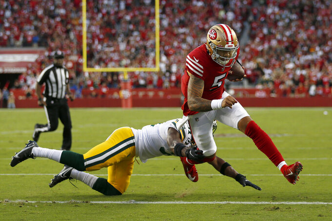 San Francisco 49ers quarterback Trey Lance (5) runs for a touchdown against Green Bay Packers strong safety Adrian Amos during the first half of an NFL football game in Santa Clara, Calif., Sunday, Sept. 26, 2021. (AP Photo/Jed Jacobsohn)