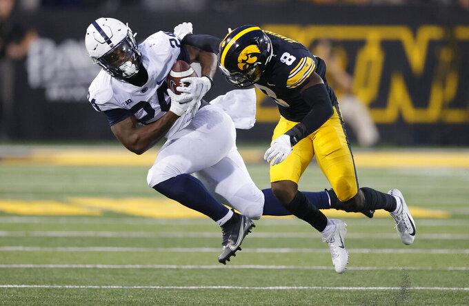 Iowa defensive back Matt Hankins (8) stops Penn State running back Keyvone Lee (24) during the second half of an NCAA college football game, Saturday, Oct. 9, 2021, in Iowa City, Iowa. Iowa won 23-20. (AP Photo/Matthew Putney)