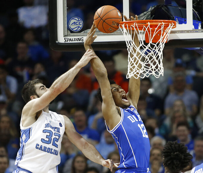 Duke's Javin DeLaurier (12) is fouled by North Carolina's Luke Maye (32) during the first half of an NCAA college basketball game in the Atlantic Coast Conference tournament in Charlotte, N.C., Friday, March 15, 2019. (AP Photo/Nell Redmond)