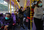 People wear protective face masks in a bus in Hong Kong, Tuesday, Feb. 4, 2020. Hong Kong on Tuesday reported its first death from a new virus, a man who had traveled from the mainland city of Wuhan that has been the epicenter of the outbreak. (AP Photo/Vincent Yu)