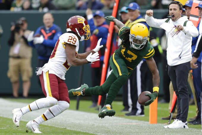 Green Bay Packers' Davante Adams is pushed out of bounds by Washington Football Team's Kendall Fuller after making a catch during the second half of an NFL football game Sunday, Oct. 24, 2021, in Green Bay, Wis. (AP Photo/Matt Ludtke)
