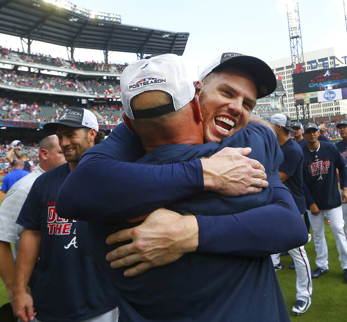 Atlanta Braves first baseman Freddie Freeman, right, hugs manager Brian Snitker after defeating Philadelphia Phillies 5-3 in a baseball game to clinch the National League East Division, Saturday, Sept. 22, 2018, in Atlanta. (AP Photo/John Bazemore)