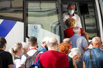 A bus driver looks at passengers entering a bus in Ljubljana, Wednesday, Sept. 15, 2021. Slovenia has introduced a mandatory anti-COVID vaccination for all civil service employees, further tightening anti-coronavirus measures that have triggered a major riot in the small Alpine state. The measure passed Friday Sept. 17, 2021 says that all state administration employees will need to be vaccinated with one shot by Oct. 1 and by Nov. 1 with the second, unless it's the one-dose Johnson & Johnson vaccine. (AP Photo)