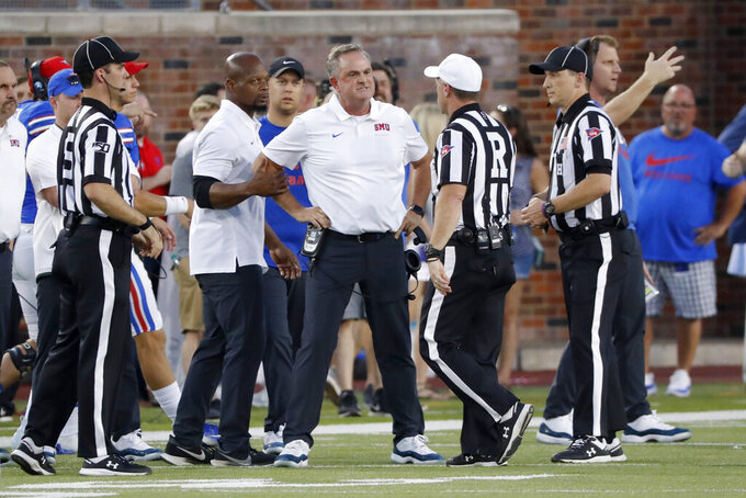 SMU head coach Sonny Dykes, center, reacts after receiving a penalty in the first half of an NCAA college football game against Tulsa, Saturday, Oct. 5, 2019, in Dallas, Texas. (AP Photo/Roger Steinman)