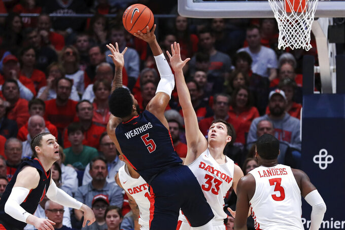 Duquesne's Marcus Weathers (5) takes a shot against Dayton's Ryan Mikesell (33) in the first half of an NCAA college basketball game, Saturday, Feb. 22, 2020, in Dayton, Ohio. (AP Photo/Aaron Doster)
