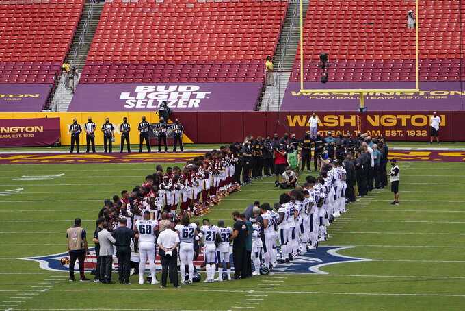 Members of the Washington Football Team and Philadelphia Eagles form an oval on the field before the start of an NFL football game, Sunday, Sept. 13, 2020, in Landover, Md. (AP Photo/Susan Walsh)