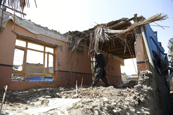 """In this Tuesday, Sept. 10, 2019, photo, Samiullah inspects the remains of his damaged house after a large explosion last week near a compound housing several foreign organizations and guesthouses, in Kabul, Afghanistan. President Donald Trump says U.S.-Taliban talks on ending the war in Afghanistan are """"dead,"""" deeply unfortunate wording for the Afghan civilians who have been killed by the tens of thousands over almost 18 years. (AP Photo/Rahmat Gul)"""
