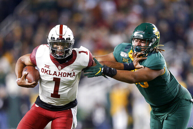 Oklahoma quarterback Jalen Hurts (1) stiff arms Baylor defensive tackle TJ Franklin (90) during an NCAA college football game, Saturday, Nov. 16, 2019, in Waco, Texas. Oklahoma won 34-31. (Ian Maule/Tulsa World via AP)