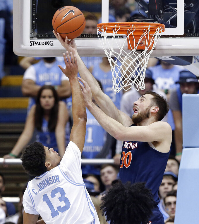 North Carolina's Cameron Johnson (13) defends while Virginia's Jay Huff (30) shoots during the first half of an NCAA college basketball game in Chapel Hill, N.C., Monday, Feb. 11, 2019. (AP Photo/Gerry Broome)