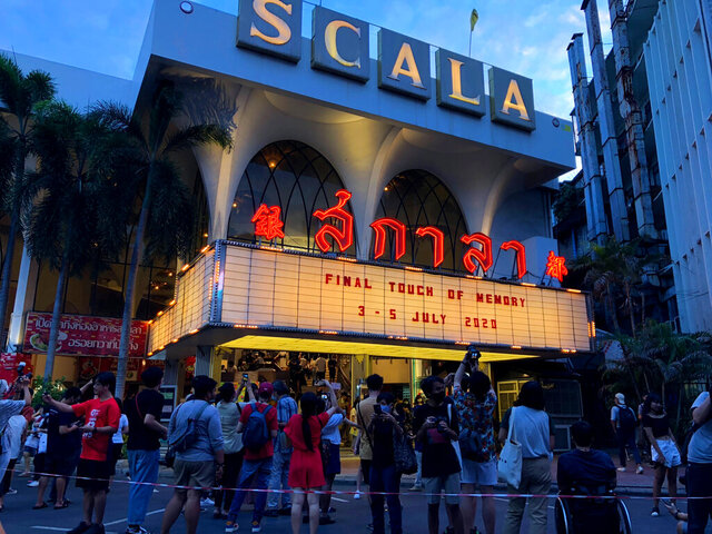 A crowd gathers to take photos of the cinema marquee of the Scala theater during its final movie screening Sunday, July 5, 2020 in Bangkok, Thailand. The Scala theater has shut its doors after 51 years as a shrine for Thai movie-goers. (AP Photo/Jerry Harmer)