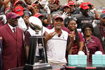 Alabama A&M coach Connell Maynor and the team await being given the Southwestern Athletic Conference championship trophy following an NCAA college football game against Arkansas-Pine Bluff, Saturday, May 1, 2021, in Jackson, Miss. Alabama A&M won 40-33. (AP Photo/Rogelio V. Solis)