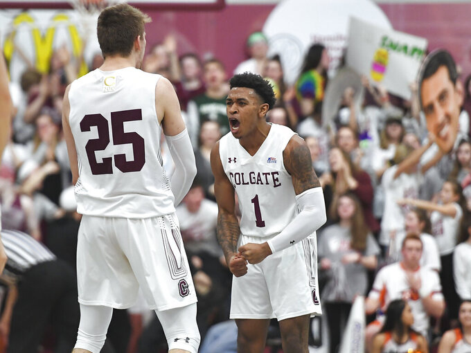 Colgate guard Jordan Burns (1) celebrates a basket with forward Rapolas Ivanauskas (25) during the first half of an NCAA college basketball game against Bucknell for the championship of the Patriot League men's tournament in Hamilton, N.Y., Wednesday, March 13, 2019. (AP Photo/Adrian Kraus)