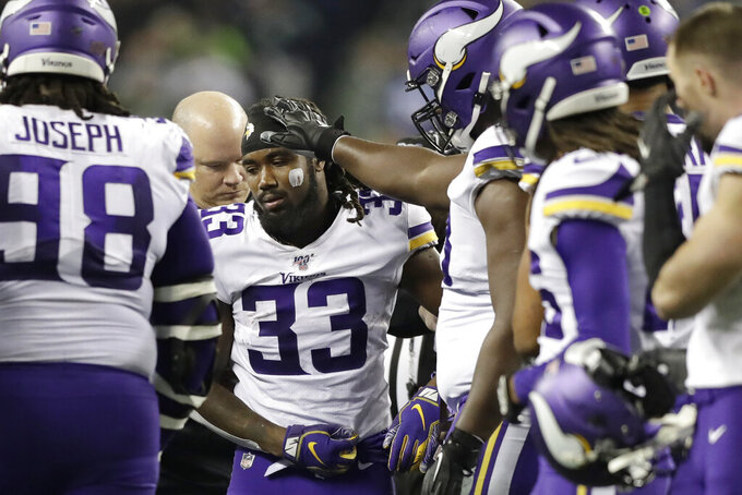 Minnesota Vikings's Dalvin Cook (33) heads off the field after being injured during the second half of an NFL football game against the Seattle Seahawks, Monday, Dec. 2, 2019, in Seattle. (AP Photo/John Froschauer)