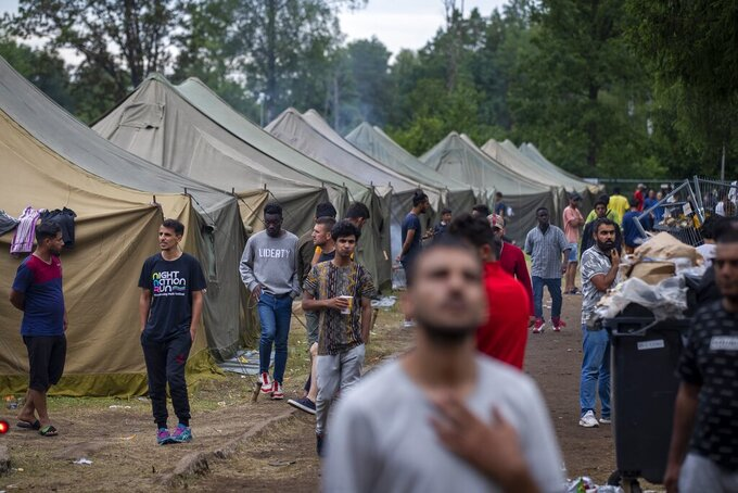 FILE - In this file photo taken on Wednesday, Aug. 4, 2021, Migrants walk at the newly built refugee camp in the Rudninkai military training ground, some 38km (23,6 miles) south from Vilnius, Lithuania. Lithuanian authorities said Friday that the Baltic country has stemmed the flow of third country migrants illegally crossing from neighboring Belarus, saying the influx of people knocking at the external border of European Union seems to have halted and hundreds have been turned away. (AP Photo/Mindaugas Kulbis, File)