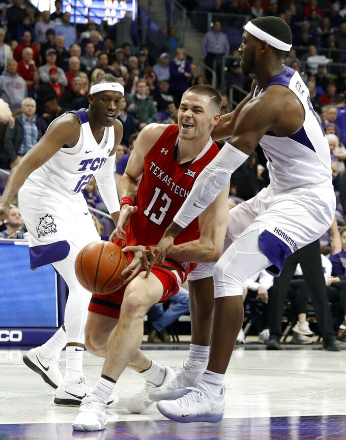TCU forward Kouat Noi watches as forward JD Miller, right, strips the ball away from Texas Tech guard Matt Mooney (13) on a drive to the basket in the first half of an NCAA college basketball game in Fort Worth, Texas, Saturday, March 2, 2019. (AP Photo/Tony Gutierrez)