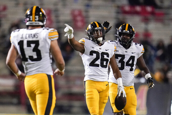 FILE - Iowa defensive back Kaevon Merriweather (26) reacts after making an interception on a pass from Maryland quarterback Taulia Tagovailoa, not visible, during the second half of an NCAA college football game in College Park, Md., in this Friday, Oct. 1, 2021, file photo. Iowa defensive end Joe Evans (13) and linebacker Jay Higgins (34) look on. The key matchup in fourth-ranked Penn State's showdown with No. 3 Iowa pits the Nittany Lions' passing combo of Sean Clifford and Jahan Dotson against a defense that leads the nation with 12 interceptions. (AP Photo/Julio Cortez, File)