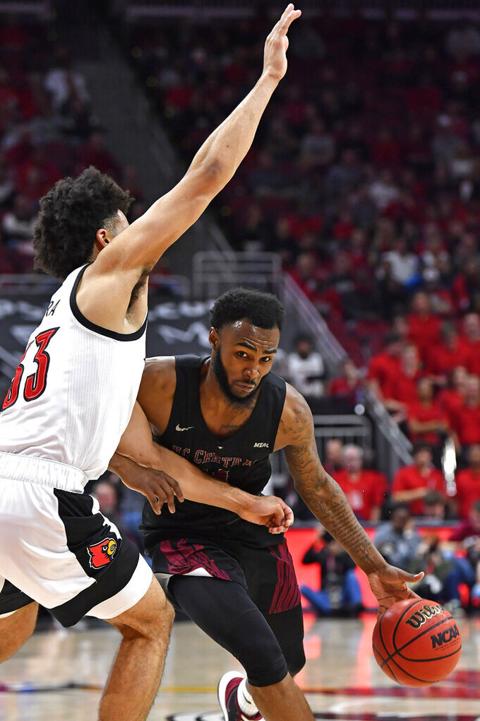 North Carolina Central guard Randy Miller Jr. , right, attempts to drive around the defense of Louisville forward Jordan Nwora (33) during the first half of an NCAA college basketball game in Louisville, Ky., Sunday, Nov. 17, 2019. (AP Photo/Timothy D. Easley)