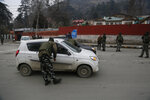 An Indian paramilitary soldier stops civil vehicles as a convoy of New Delhi-based diplomats passes through Srinagar, Indian controlled Kashmir, Thursday, Jan. 9, 2020. Envoys from 15 countries including the United States are visiting Indian-controlled Kashmir starting Thursday for two days, the first by New Delhi-based diplomats since India stripped the region of its semi-autonomous status and imposed a harsh crackdown in early August. (AP Photo/Mukhtar Khan)