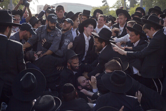 "FILE - In this Oct. 19, 2017 file photo, Israeli police scuffle with ultra-Orthodox Jews as they block a main road during a protest against Israeli army conscription, in Jerusalem. The Israeli military said Thursday, Feb. 20, 2020, that it found ""serious, systemic failures"" in its own reporting that inflated figures on the enlistment of ultra-Orthodox Jews, a hot-button issue in a country where most Jewish men are subject to mandatory conscription. Military draft exemptions for ultra-Orthodox men have long been a source of resentment among Israel's Jewish secular majority, who are required to serve. The issue is expected to be key in upcoming March 2 elections. (AP Photo/Ariel Schalit, File)"