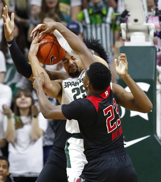 Rutgers guard Montez Mathis (23) reaches in on Michigan State forward Kenny Goins (25) during the first half of an NCAA college basketball game Wednesday, Feb. 20, 2019, in East Lansing, Mich. (AP Photo/Carlos Osorio)