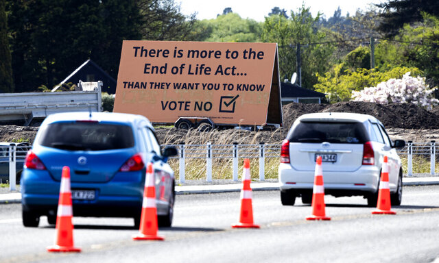 FILE - In this Oct. 16, 2020, file photo, cars are driven past a billboard urging voters to vote