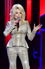 In this Saturday, Oct. 12, 2019, photo Dolly Parton performs at her 50th Opry Member Anniversary at the Grand Ole Opry in Nashville, Tenn. The73-year-old actress, singer and songwriter, who first played the Opry when she was just a teenager, celebrated her 50th anniversary as a Grand Ole Opry member on Saturday. (Larry McCormack/The Tennessean via AP)