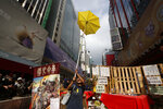 FILE - In this file photo taken Wednesday, Nov. 26, 2014, a protester holds a yellow umbrella, the symbol of Hong Kong's pro-democracy movement, at the barricades as the police keep clearing them away at an occupied area in Mong Kok district of Hong Kong. A legislative bill that harkened back on Beijing's promise to allow Hong Kong residents to vote for their leader, triggered massive demonstrations in Hong Kong's most crowded districts, led by young activists and lasting 79 days. The movement's organizers called it