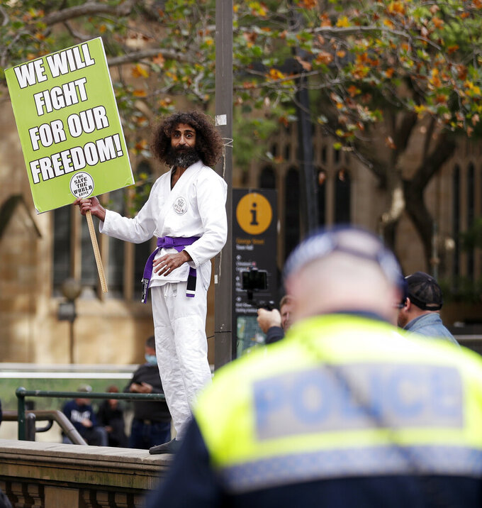 A man dressed in a martial arts uniform addresses supporters as protesters gather in Sydney, Saturday, June 13, 2020, during a day of demonstrations across Australia in support of the Black Lives Matter movement and refugee rights. Protesters in Sydney, Adelaide and Perth were urged to stay away by government officials concerned about the risk of spreading the new coronavirus. (AP Photo/Rick Rycroft)