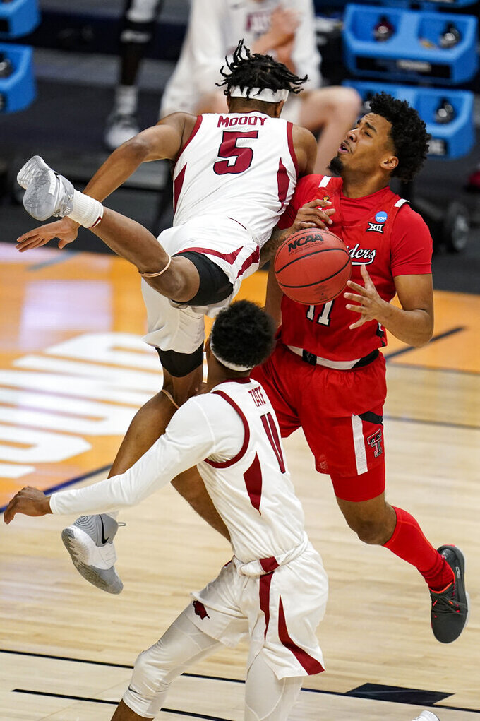 Arkansas guard Moses Moody (5) and Texas Tech guard Micah Peavy (5) collide in the first half of a second-round game in the NCAA men's college basketball tournament at Hinkle Fieldhouse in Indianapolis, Sunday, March 21, 2021. (AP Photo/Michael Conroy)