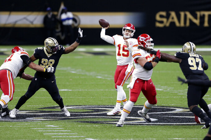 Kansas City Chiefs quarterback Patrick Mahomes (15) passes under pressure from New Orleans Saints defensive tackle Sheldon Rankins (98) and defensive tackle Malcolm Roach (97) in the first half of an NFL football game in New Orleans, Sunday, Dec. 20, 2020. (AP Photo/Butch Dill)