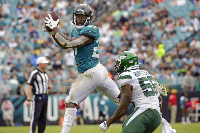 Jacksonville Jaguars running back Leonard Fournette, left, makes a reception in front of New York Jets linebacker James Burgess during the first half of an NFL football game, Sunday, Oct. 27, 2019, in Jacksonville, Fla. (AP Photo/Phelan M. Ebenhack)