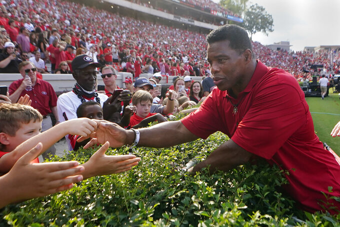 Former Georgia running back and Republican candidate for U.S. Senate, Herschel Walker greets fans at halftime of an NCAA college football game between Georgia and UAB, Saturday, Sept. 11, 2021, in Athens, Ga. (AP Photo/John Bazemore)