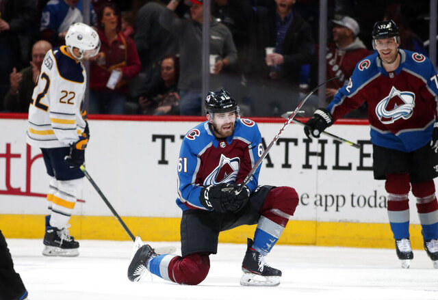 Colorado Avalanche right wing Martin Kaut, center, celebrates after his first professional goal as right wing Joonas Donskoi, back right, and Buffalo Sabres center Johan Larsson look on in the second period of an NHL hockey game Wednesday, Feb. 26, 2020, in Denver. (AP Photo/David Zalubowski)