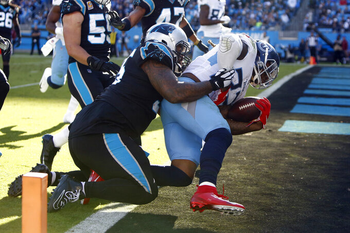 Tennessee Titans running back Derrick Henry (22) scores while Carolina Panthers defensive tackle Dontari Poe (95) tackles during the second half of an NFL football game in Charlotte, N.C., Sunday, Nov. 3, 2019. (AP Photo/Brian Blanco)