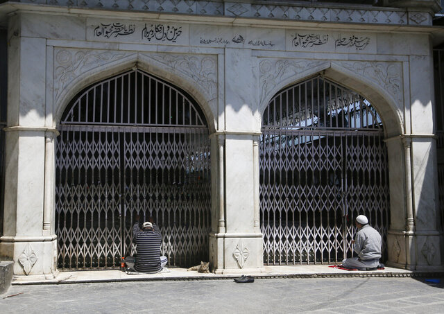 Kashmiri Muslims pray outside the closed gate of a muslim shrine during the holy fasting month of Ramadan in Srinagar, Indian controlled Kashmir, Friday, May 8, 2020. Religious clerics and authorities in Indian portion of Kashmir have urged people to pray inside their homes to prevent spread of coronavirus in the region. Muslims across the world are observing the holy fasting month of Ramadan, where they refrain from eating, drinking and smoking from dawn to dusk. (AP Photo/Mukhtar Khan)