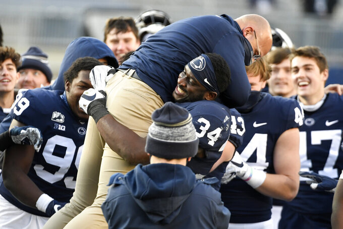 Penn State head coach James Franklin jumps into the arms of defensive end Shane Simmons (34 )while celebrating a victory over Michigan State following an NCAA college football game in State College, Pa., on Saturday, Dec. 12, 2020. (AP Photo/Barry Reeger)
