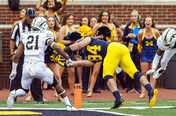 Michigan tight end Sean McKeon (84) dives for a 17-yard touchdown, defended by Western Michigan defensive back Stefan Claiborne (21), in the first quarter of an NCAA college football game in Ann Arbor, Mich., Saturday, Sept. 8, 2018. (AP Photo/Tony Ding)