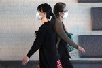 Women wearing protective masks to help curb the spread of the coronavirus walk Friday, Oct. 16, 2020, in Tokyo. The Japanese capital confirmed more than 180 new coronavirus cases on Friday. (AP Photo/Eugene Hoshiko)