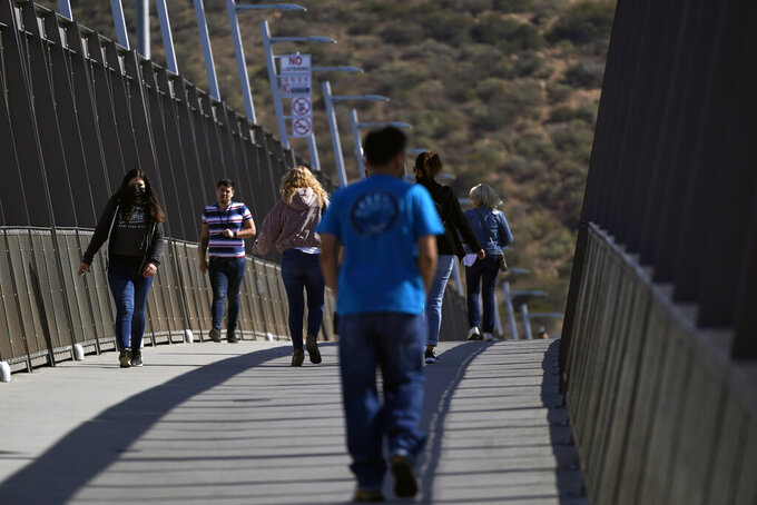 People walk on a bridge at the San Ysidro Port of Entry, connecting Tijuana, Mexico, to the United States, Wednesday, Oct. 13, 2021, in San Diego. Beleaguered business owners and families separated by COVID-19 restrictions rejoiced Wednesday after the U.S. said it will reopen its land borders to nonessential travel next month, ending a 19-month freeze. (AP Photo/Gregory Bull)